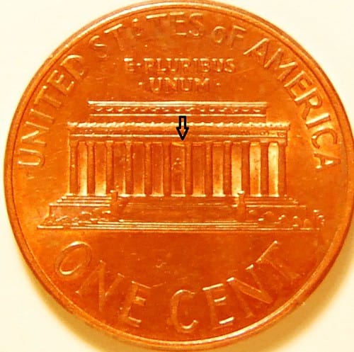 Close image of penny with arrow indicating where a mint error is on the coin