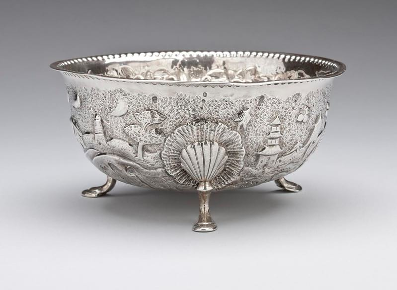 Antique silver bowl with intricate carvings on the side